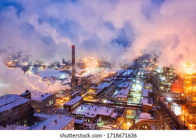 Aerial view of steel plant at night with smokestacks and fire blazing out of the pipe. Industrial panoramic landmark with blast furnance of metallurgical production