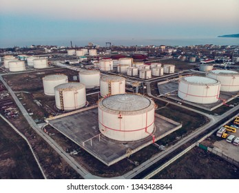 Aerial view of steel round Oil Storage Tanks or Reservoirs at sunset. Oil refinery industry, petroleum and petrochemical plant, drone shot