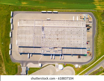 Aerial view of storage and freight terminal with trucks. Industrial background. Logistics from above.