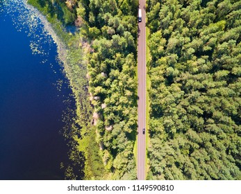 Aerial view of straight road through the mixed forest by the lakeshore, Mazury, Poland