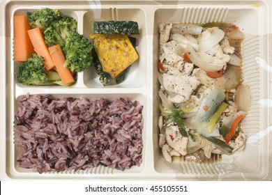 Aerial view of streamed carrot, broccoli, pumpkin, riceberry and fried chilli black paper with chicken and onion in the box. Breakfast, lunch and dinner.