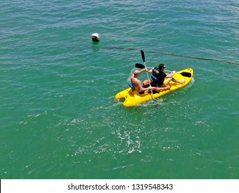 Aerial view view of strong young active men kayaking on the clear blue  turquoise water of the ocean. Active vacation. Praia do Forte, Brazil. 02/11/2019
