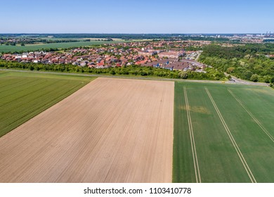 Aerial view of a suburb on the outskirts of Wolfsburg in Germany, with terraced houses, semi-detached houses and detached houses, arable land in the foreground, made with drone