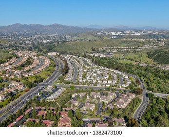 Aerial view suburban neighborhood with identical villas next to each other in the valley. San Diego, California, USA. Aerial view of residential modern subdivision luxury house with swimming pool.