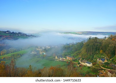 An aerial view of the suburbs of Stroud in autumn and a foggy Stroud valley from Rodborough Common, The Cotswolds, Gloucestershire, United Kingdom