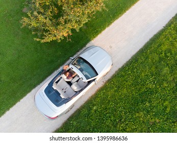 Aerial view of successful man driving and enjoying his silver convertible luxury sports car on the open country side road.