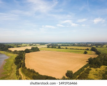 Aerial view of the Suffolk countryside with a recently harvested hay field in the foreground