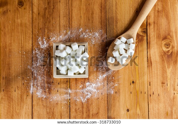 Aerial View of Sugar Cubes in Square Shaped Bowl and Spoon with Unrefined Sugar spill over in Wooden Background