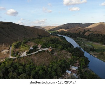 Aerial view of Sumba island landscape surrounded by hills, river and Sumba traditional houses in Sumba Island, East Nusa Tenggara Indonesia