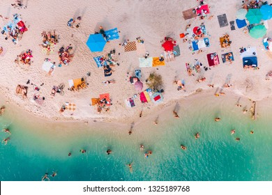 aerial view of sunny sandy beach with blue azure water. summer vacation