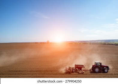 Aerial view of the sunset above the tractor harrowing the large brown field in spring season