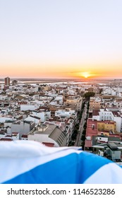 Aerial view of the sunset in Huelva, with the white and blue flag of the city