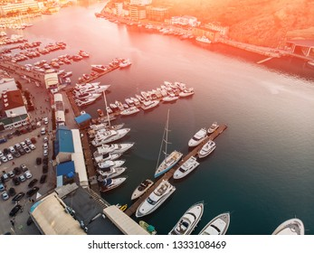 Aerial view of sunset over Balaklava, Crimea sea bay with many yachts and boats in resort coast between mountains. Beautiful tourist luxury European sunny town with harbour