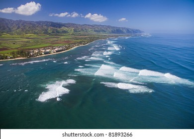 An aerial view of the surf at Waialua - North Shore of Oahu. Makuleia Beach and Kaena Point in distance.