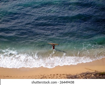 Aerial view of Surfer carrying surfboard into water, Diamond Head Beach, Hawaii