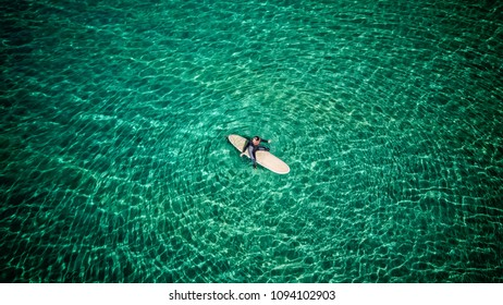 Aerial view of a surfer girl waiting for a wave at a paradise beach in Galicia, Spain.