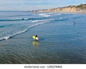 Aerial view of surfer in wet suit holding a surfboard on the beach. Surfer going to the water, on La Jolla Beach, California, located in San Diego County. USA. 01/04/2019