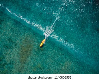 Aerial view with surfer woman on wave in tropical blue ocean. Top view