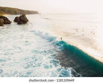 Aerial view with surfers and barrel wave in ocean, Padang Padang