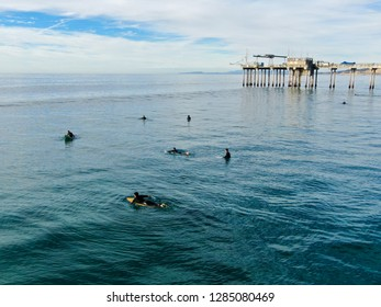 Aerial view of surfers enjoying waves in La Jolla with the scripps pier institute of oceanography on the background, La Jolla, San Diego, California, USA. 01/07/2019