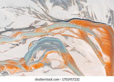 Aerial view of surrealistic patterns of tiny orange and turquoise streams at the bottom of dried up Zhinvali water reservoir in winter