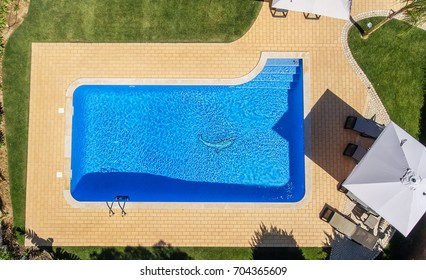 Aerial view of swimming pool outside hotel.