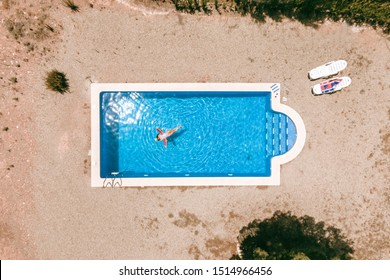 aerial view of a swimming pool in summer. Young girl in a swimsuit and hat floating with pool noodles.