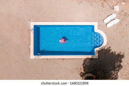aerial view of a swimming pool in summer. Young girl in a swimsuit and hat floating with pink donut.
