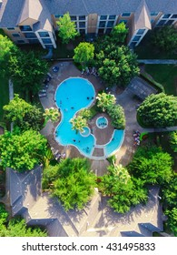 Aerial view of swimming pool in a typical multi-level apartment living in Houston, Texas, US at sunset. It surrounded by green garden, foldable chairs furniture and unidentified swimming kids.