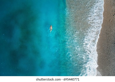 Aerial view of swimming woman in mediterranean sea in Oludeniz, Turkey. Beautiful summer seascape with girl, clear azure water, waves and sandy beach in sunny day. Top view from flying drone. Nature