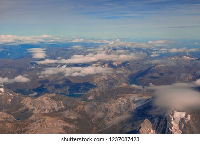 Aerial view of Swiss mountains from airplane with clouds and blue sky