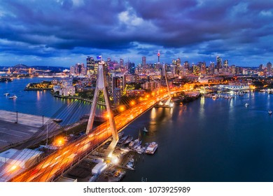 Aerial view of Sydney city CBD landmarks on Sydney harbour behind steel cables and archs of Anzac bridge highway connecting Inner West Victoria road with Western Distributor at sunset with lights.