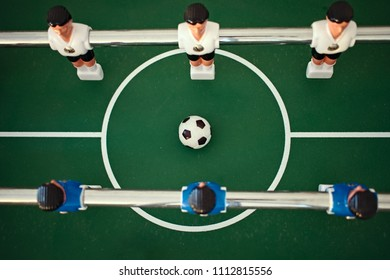 Aerial view of table football kicker with white and blue miniature figurines starting a new game