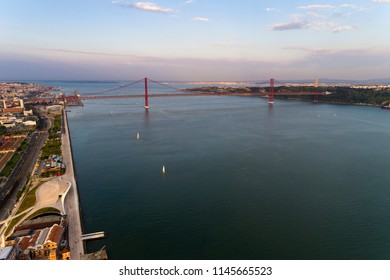Aerial view of the Tagus River (RIo Tejo) in the city of Lisbon with sail boats and the 25 of April Bridge on the background; Concept for travel in Portugal and visit Lisbon