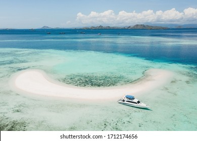Aerial view of Taka Makassar island in Komodo national park, Indonesia. Empty paradise small white sand island on coral reef. Luxury boat near beach.