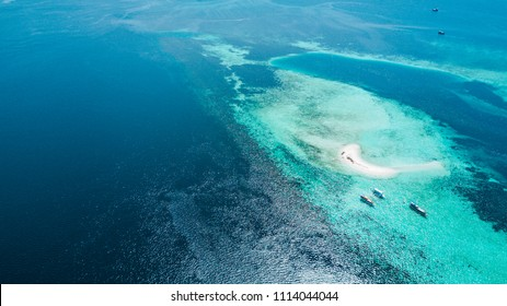 Aerial view of Taka Makassar, sand island where strong current flowing under water surface with tourist boats and turquoise sea, Komodo Island (Komodo National Park), Labuan Bajo, Flores, Indonesia