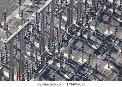 An aerial view taken from a helicopter of a high voltage power distribution substation in Britain. The DNO site has many insulator posts, bus bars and switches all seen from an elevated perspective.