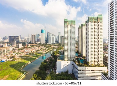 Aerial view of tall apartment buildings with the business district skyline in the background in Jakarta on a sunny day in Indonesia capital city.