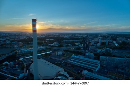 Aerial view of tall chimney of thermal power plant, painted white and red against populated city in background. Energy facility, providing heat for big city.