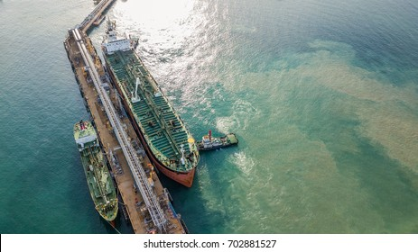 Aerial view tanker ship under cargo operations on typical shore station.