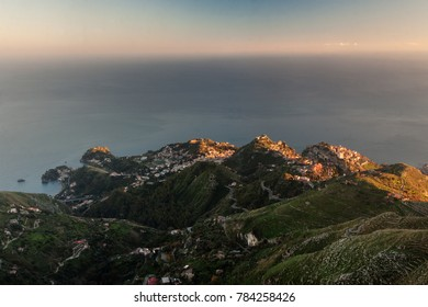 Aerial view of Taormina and Castelmola, with mediterranean sea on background. Image taken at sunset from above.
