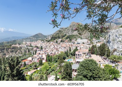 Aerial view of Taormina, historic city at the Sicilian coast of Italy with smoking Etna in the distance
