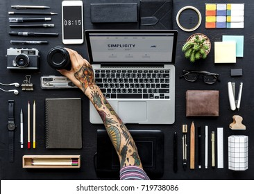 Aerial view of tattooed hand reaching for coffee