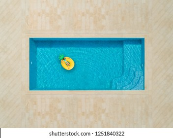 Aerial view of teenager on inflatable pineapple mattress in swimming pool.