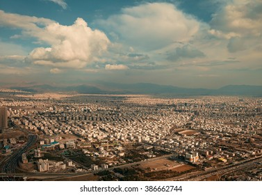 Aerial view of Tehran city against blue sky with fluffy white clouds, shot above Milad Tower.