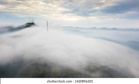Aerial view television transmission station on the mountain with fog in sunrise