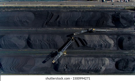 Aerial view. Of the territory of the coal terminal with coal heaps and a reclaimer. The territory of the coal seaport.