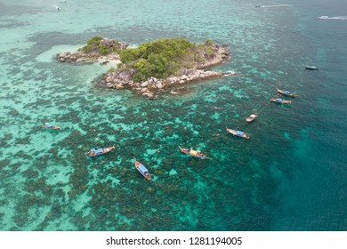 Aerial view of Thai traditional longtail boats and unidentified tourists snorkeling activity on tropical island near Lipe Island, Satun, Thailand.
