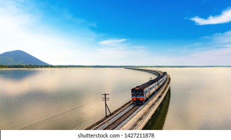 Aerial view of Thailand train pass across the lake of the dam with blue sky.Train is running on the bridge over the reservoir Pa Sak Jolasid dam at Lopburi Thailand.