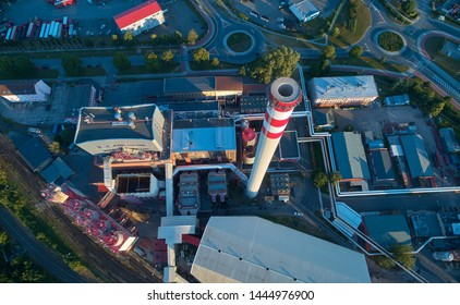 Aerial view of thermal power plant. Heating plant and its equipment, view from above. Tall chimney, painted white red. Energy facility, providing heat for big city.